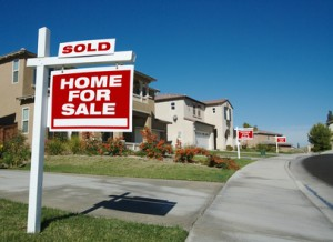 Home For Sale Signs & One Sold in Front of New Homes